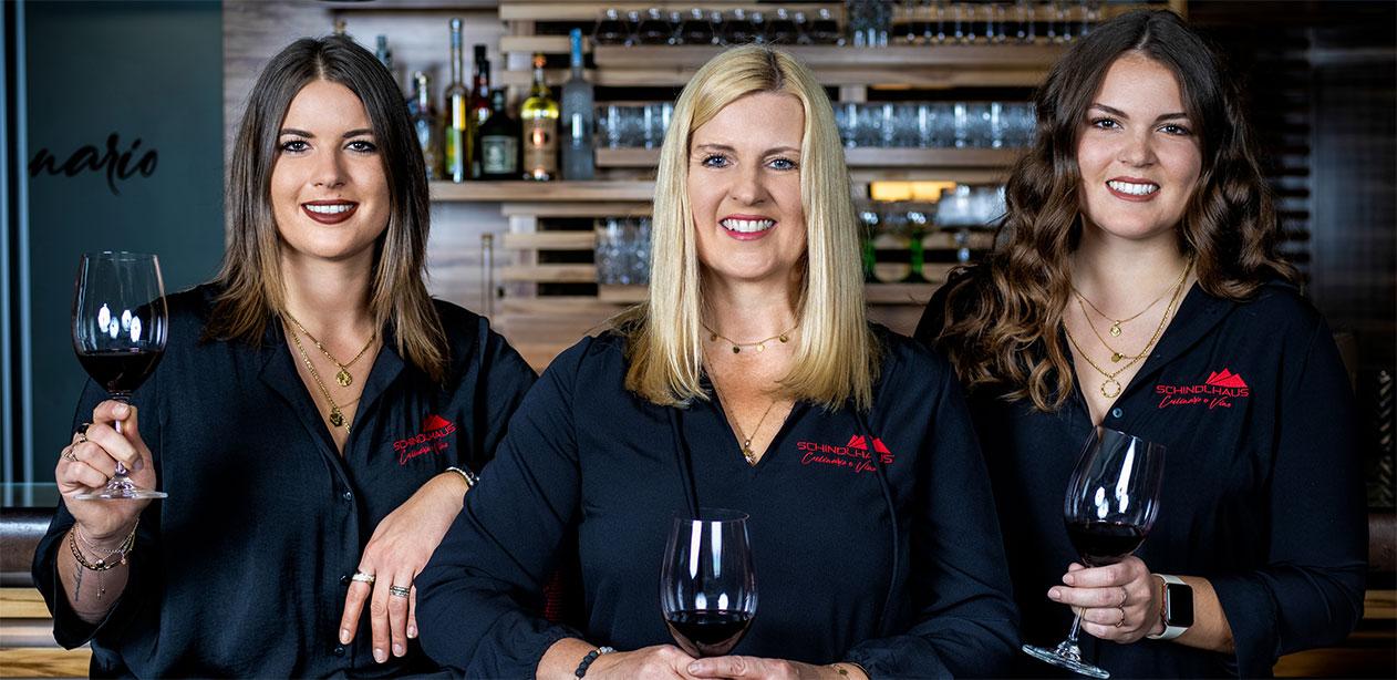 3 Frauen mit jeweils einem Glas Rotwein vor einer Bar.