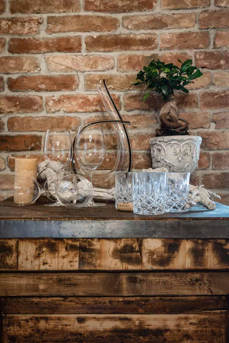 Mehrere Wein und Wassergläser vor einer Ziegelmauer.