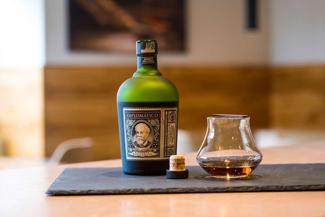 Eine Flasche Whiskey Diplomatico und daneben ein befülltes Glas.