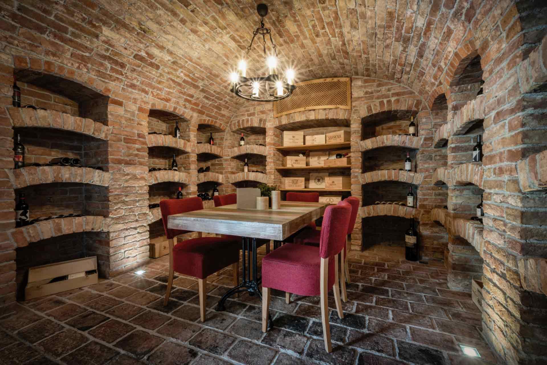Ein historische Weinkeller mit einem  Tisch und roten Stühlen in der Mitte.