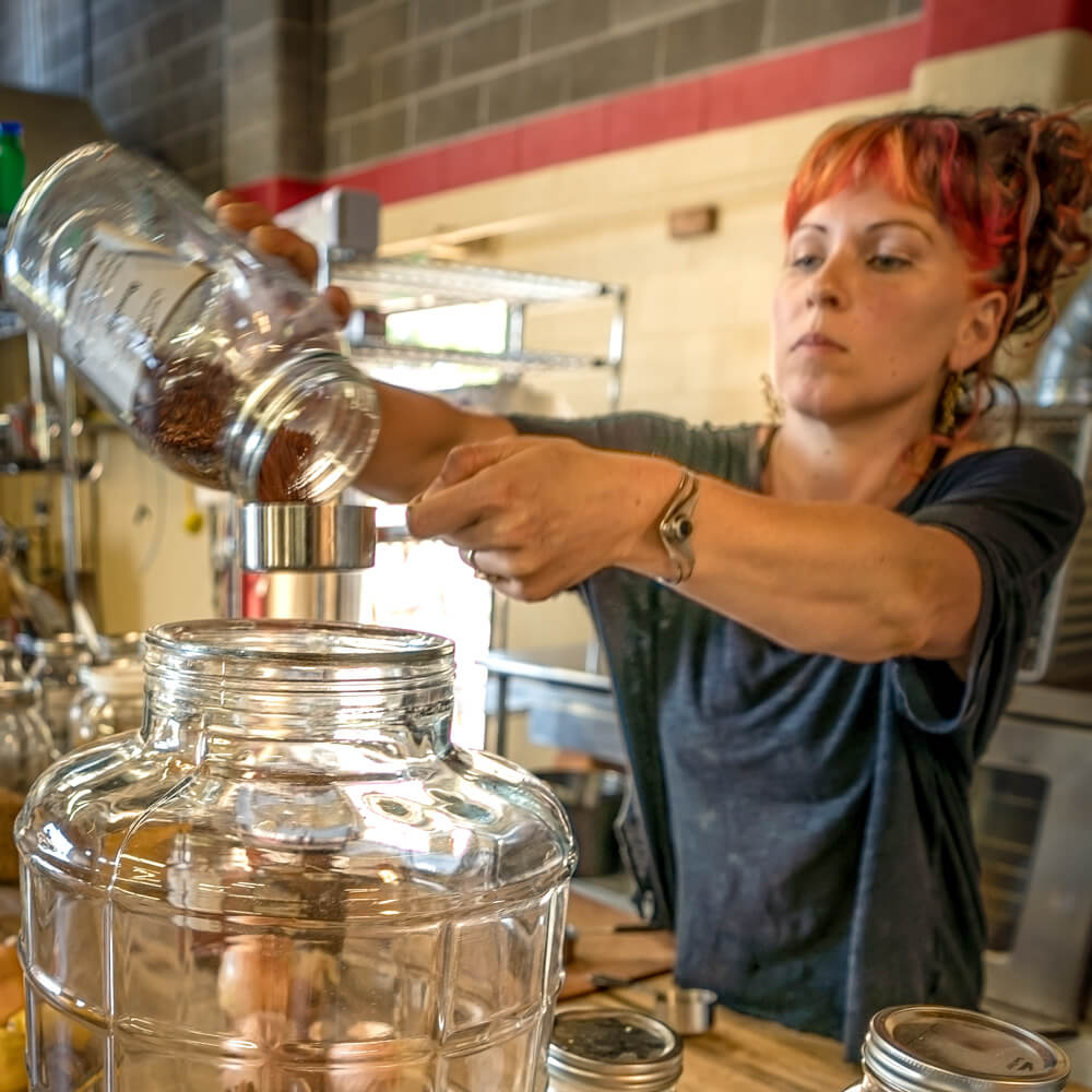 Annie pouring ingredients while making a batch of fire tonic