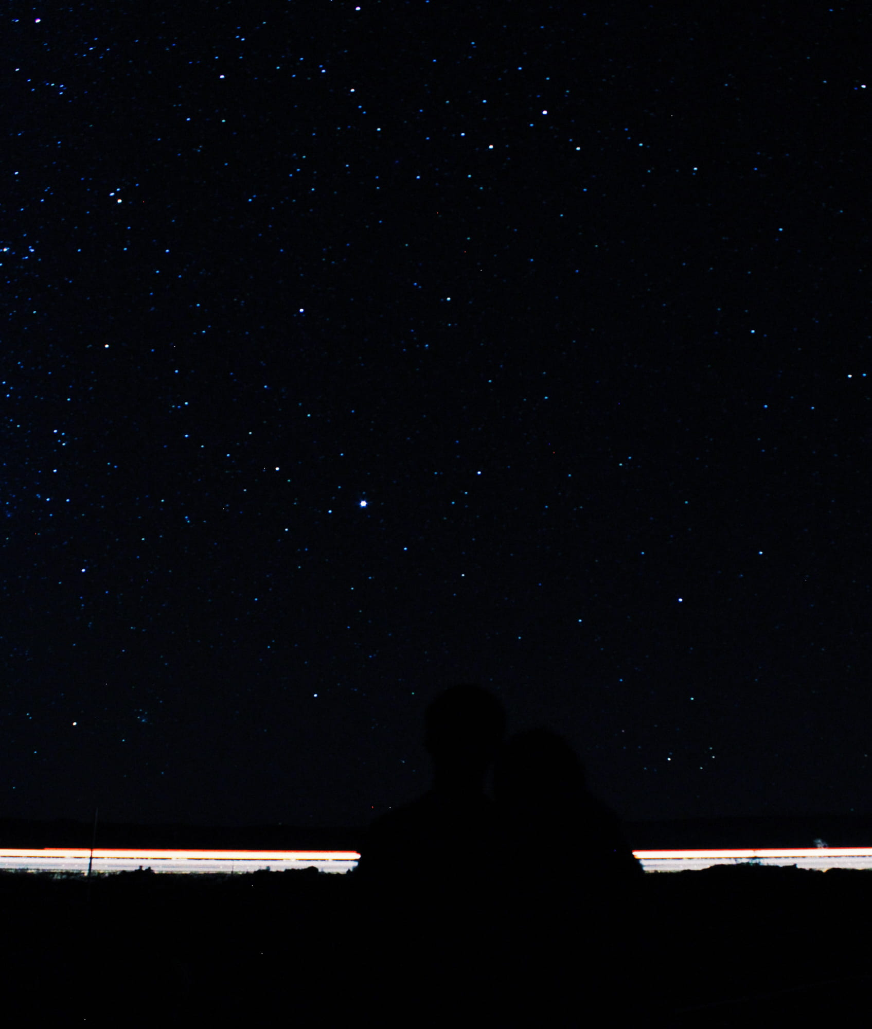 Photo of the night sky with a sliver of light on a low horizon, work by Kristen Aoyagi