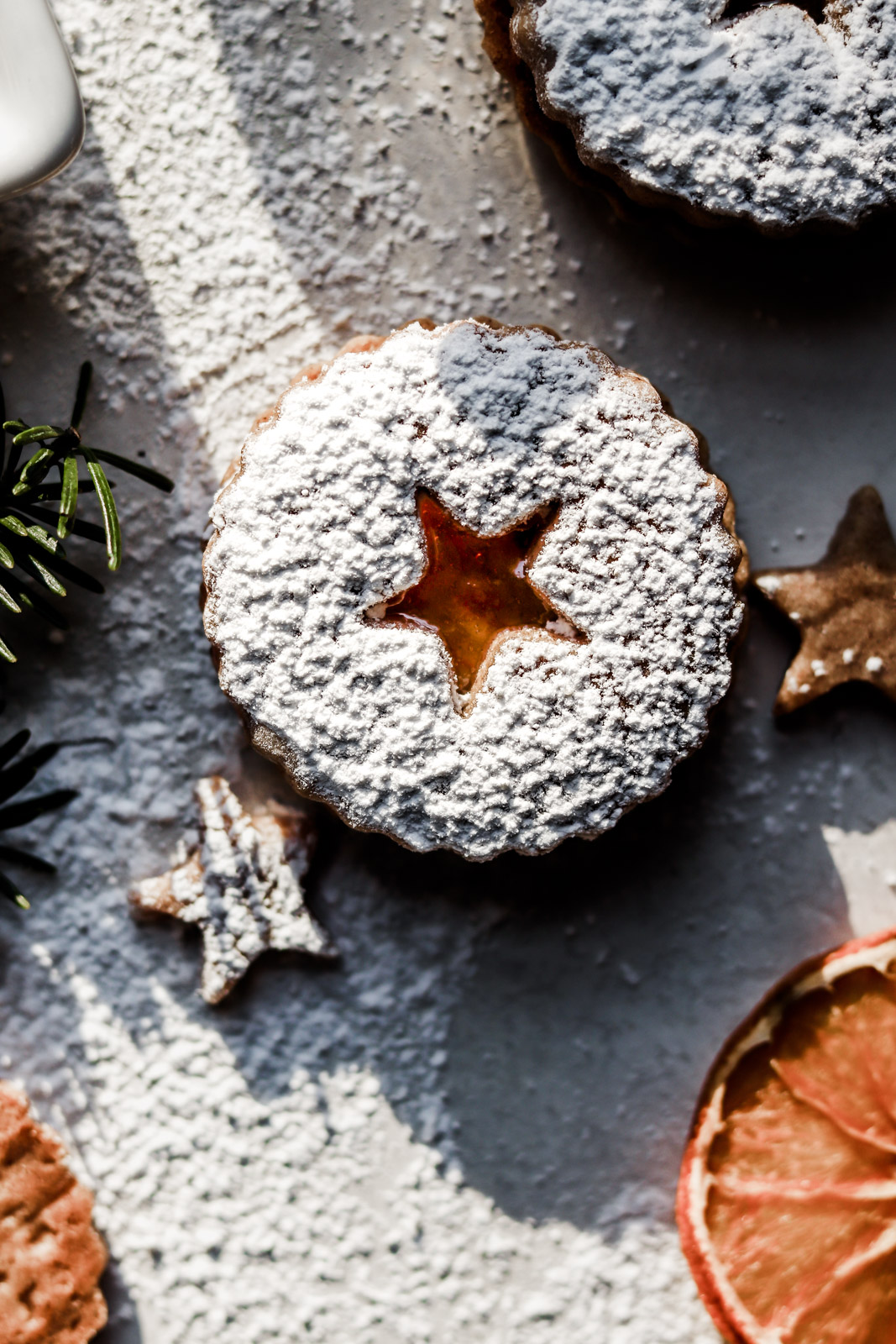 Spiced linzer cookie with a star shaped cut-out revealing the clementine marmalade inside, covered with icing sugar