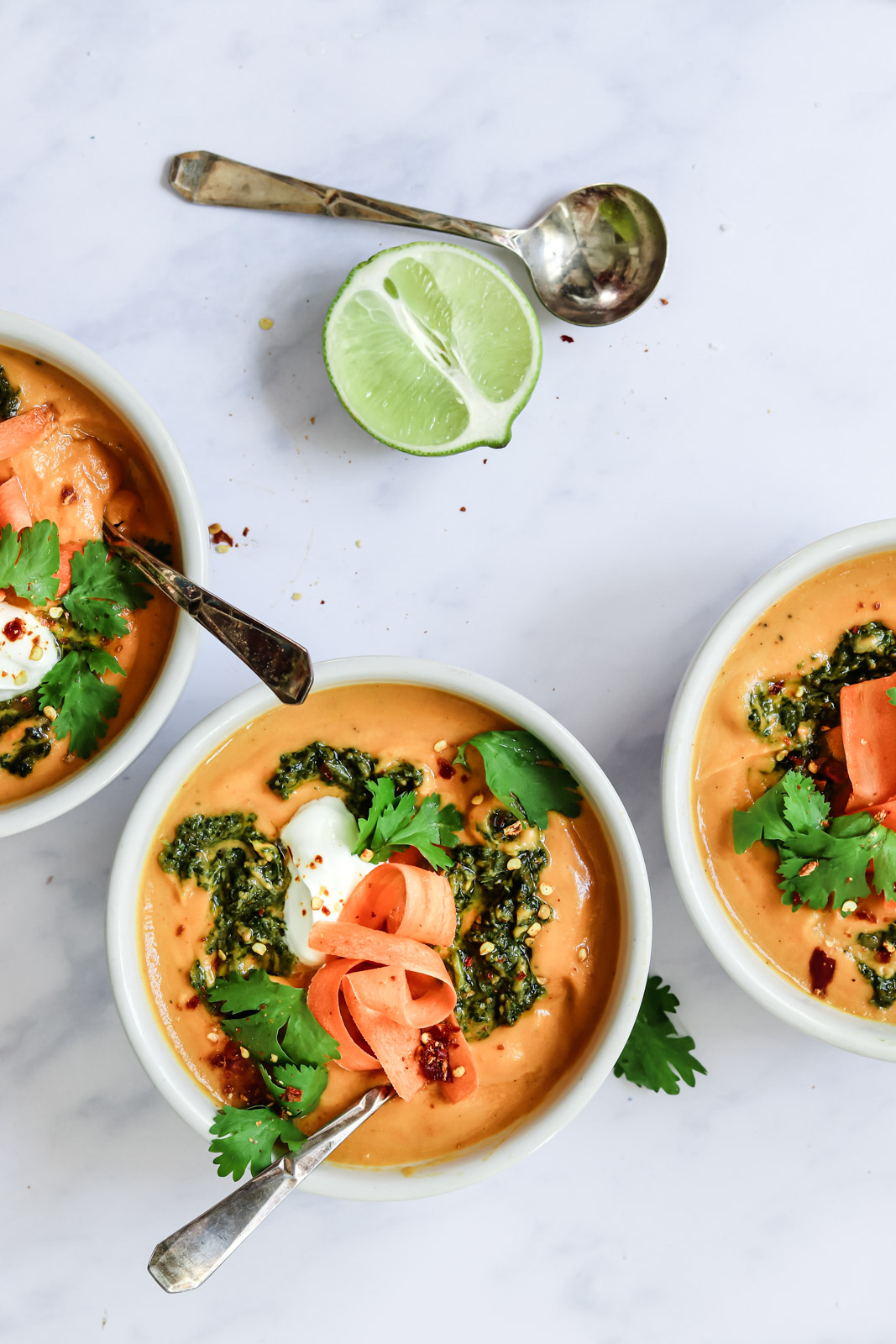 Three bowls of curried carrot coconut soup garnished with cilantro pesto and sour cream