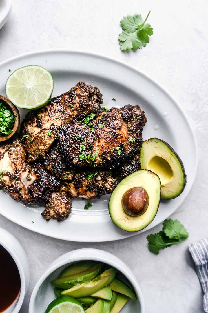 Close up of some charred jerk chicken next to a cut open avocado and a lime.