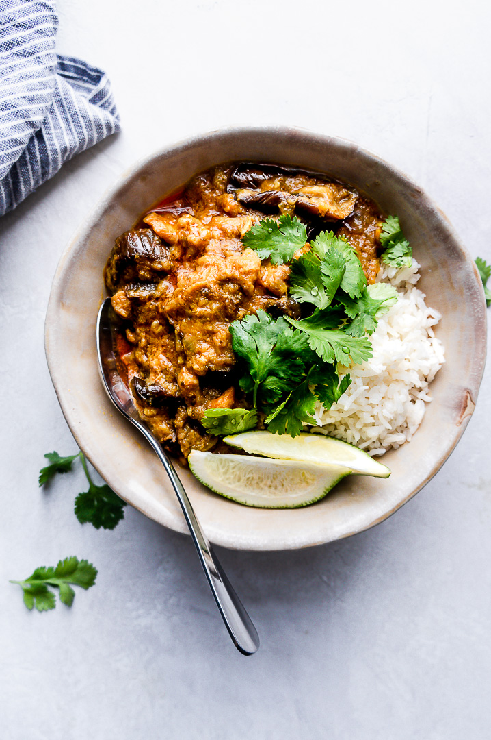 A bowl of coconut chicken curry with eggplant and rice, garnished with fresh cilantro and lime wedges