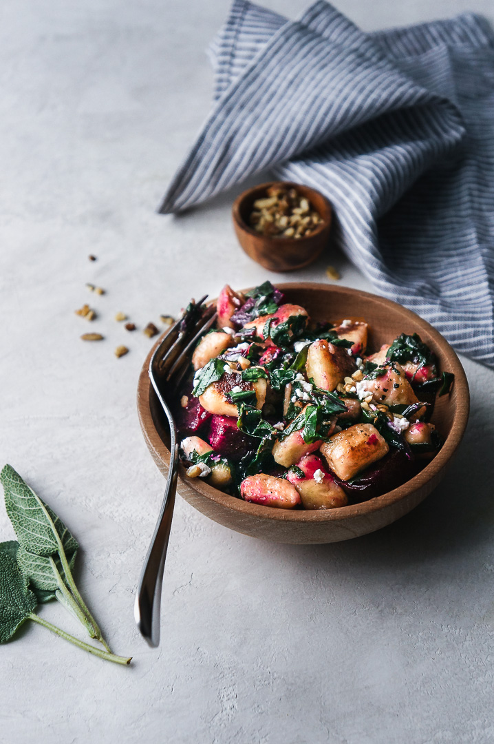 Bowl of gnocchi with roasted beets and a sage butter sauce with a striped kitchen towel, a small pinch bowl of walnuts, and a few sage leaves