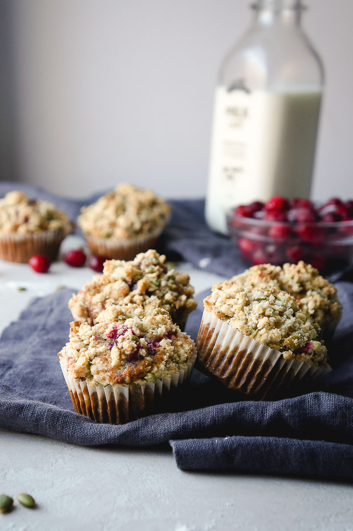 Several cranberry banana muffins on a dark grey kitchen towel with a glass bottle of milk, bowl of cranberries, and a few extra muffins in the background