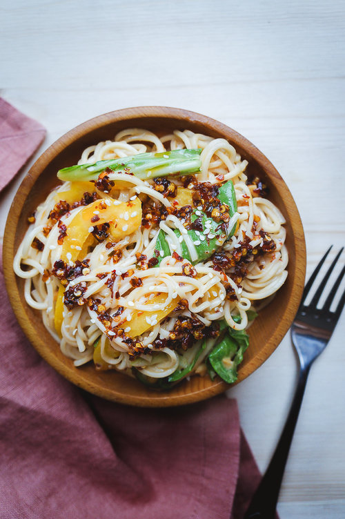 Bowl of peanut noodles with Sichuan chili oil on a table with a pink kitchen towel