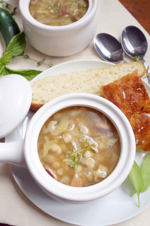 Two bowls of spicy cabbage, white bean and sausage soup with bread