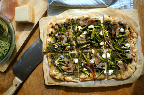 Close-up image of an asparagus pizza with spinach and beet green pesto