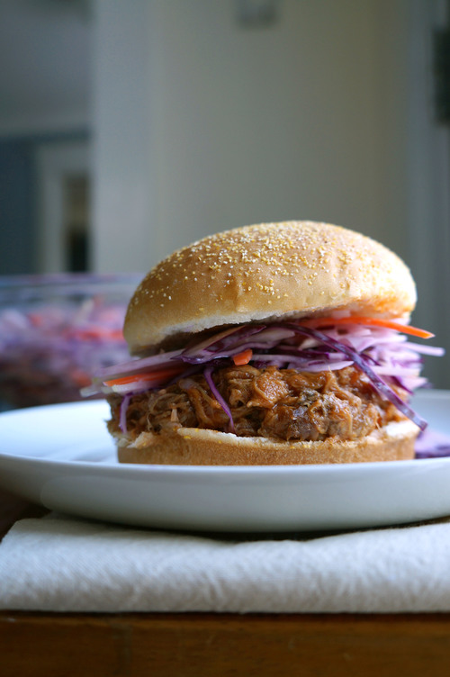 Side view of a bulled pork sandwich with kohlrabi slaw on a sesame seed bun on a plate