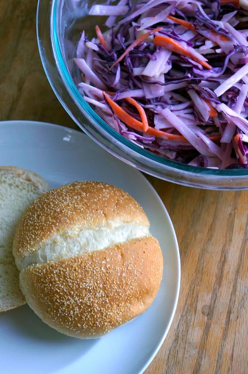 A plate with a sandwich bun and a bowl of kohlrabi slaw
