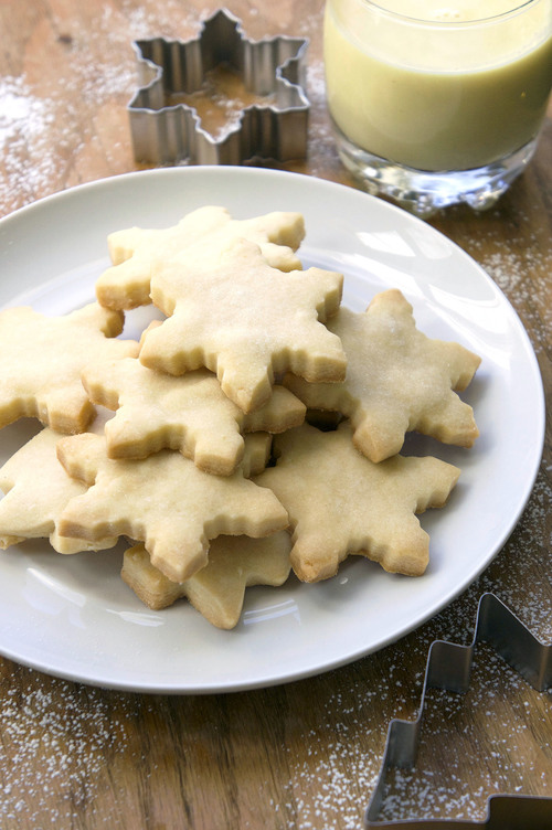 A plate of snowflake shaped shortbread cookies with a glass of eggnog and some cookie cutters