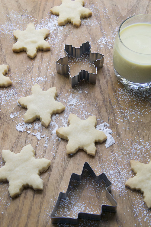 Several sugar cookies shaped like snowflakes with a glass of eggnog and a cookie cutter