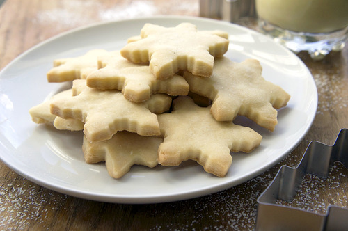 A pile of snowflake shaped sugar cookies on a plate