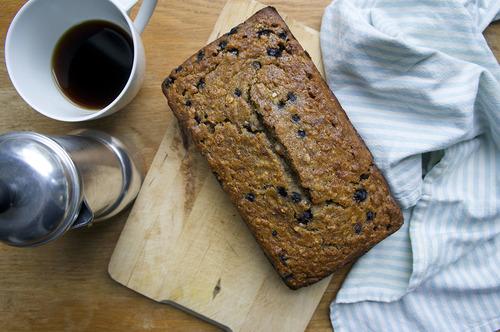 Loaf of banana bread on a cutting board with a striped kitchen towel, a coffee and a stovetop espresso maker