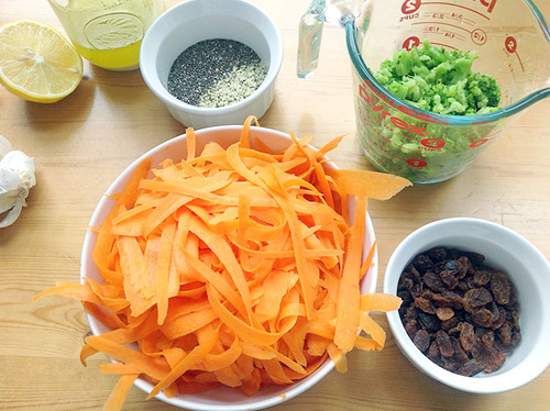 Counter filled with bowls of shaved carrots, raisins, chopped broccoli