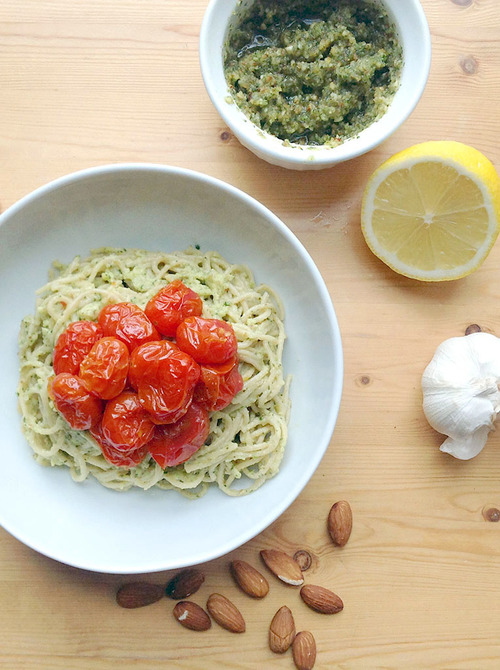 Bowl of avocado pasta with roasted cherry tomatoes and a ramekin of cilantro pesto