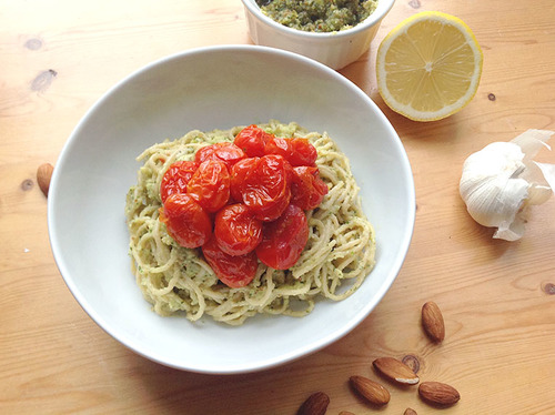 Bowl of pasta dressed in an avocado sauce topped with a pile of roasted cherry tomatoes
