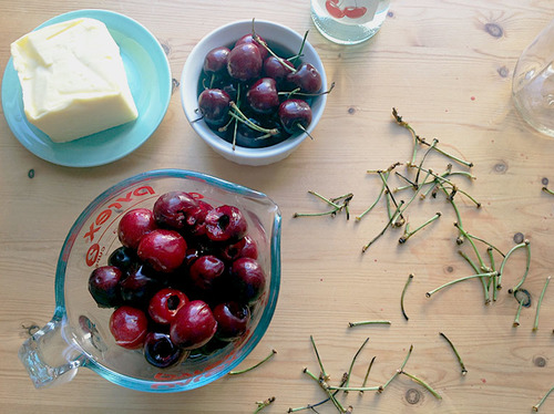 A counter filled with dishes of cherries, cherry stems and butter