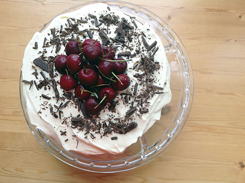 A black forest cake with a pile of cherries and shaved chocolate on top
