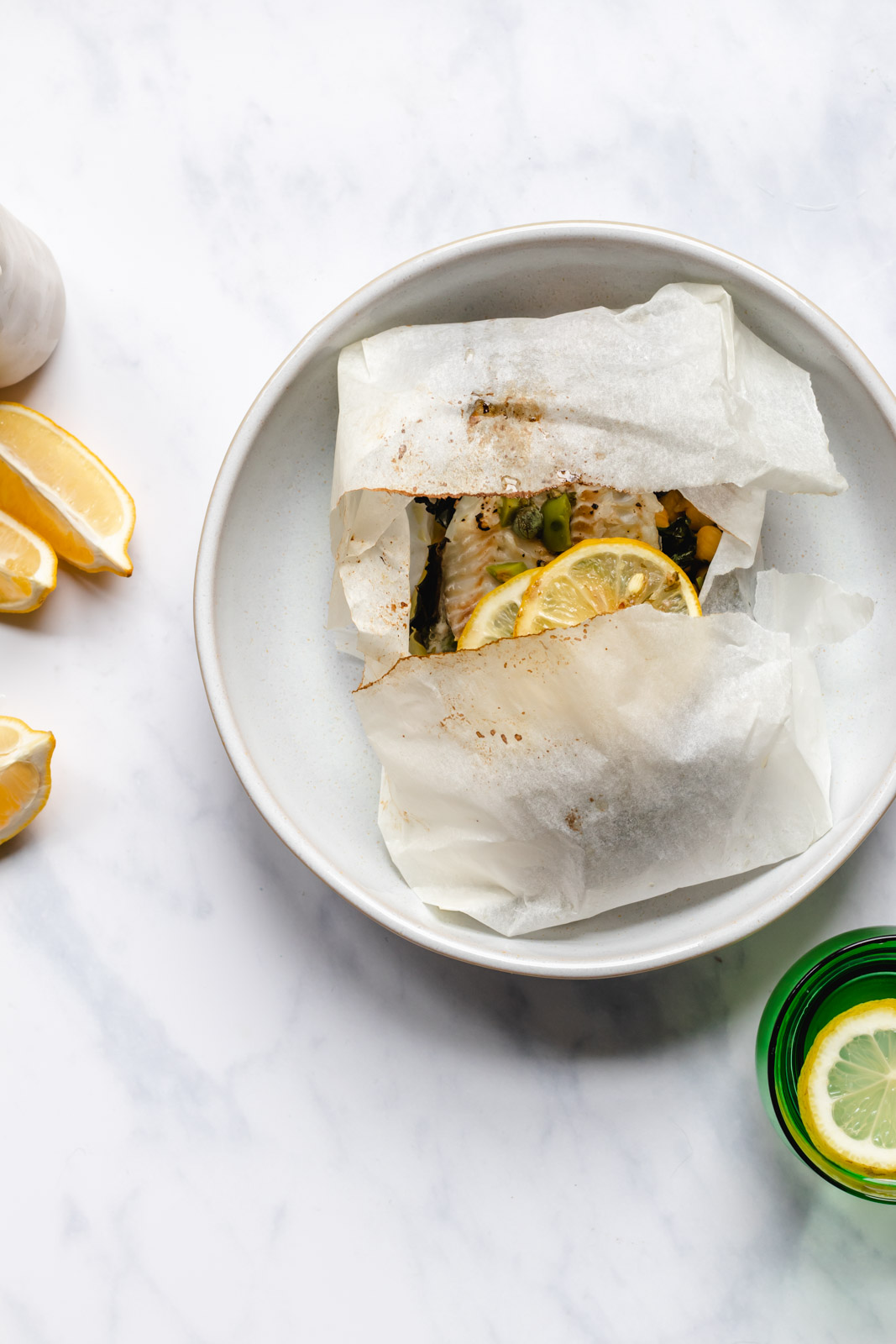 White fish en papillote with beans, greens and anchovy butter sauce in a large ceramic deep plate surrounded by lemon wedges, a glass of water and extra sauce