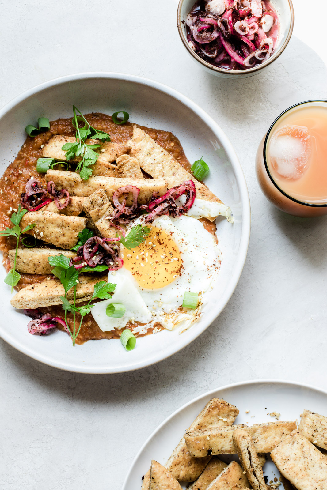 Bowl of pitaquiles topped with a fried egg and sumac onions surrounded by a small bowl of sumac onions, a glass of grapefruit juice, and a plate of pita chips