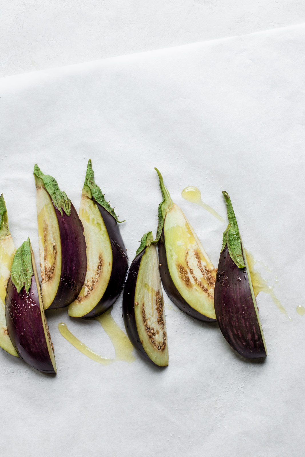 Row of purple eggplant wedges drizzled with olive oil