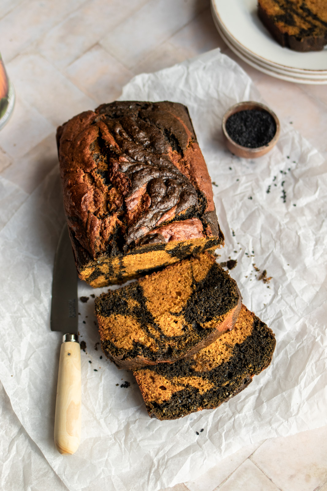 A loaf of black sesame swirl pumpkin bread sliced open and sitting on baking paper with a wooden knife and a bowl of black sesame seeds