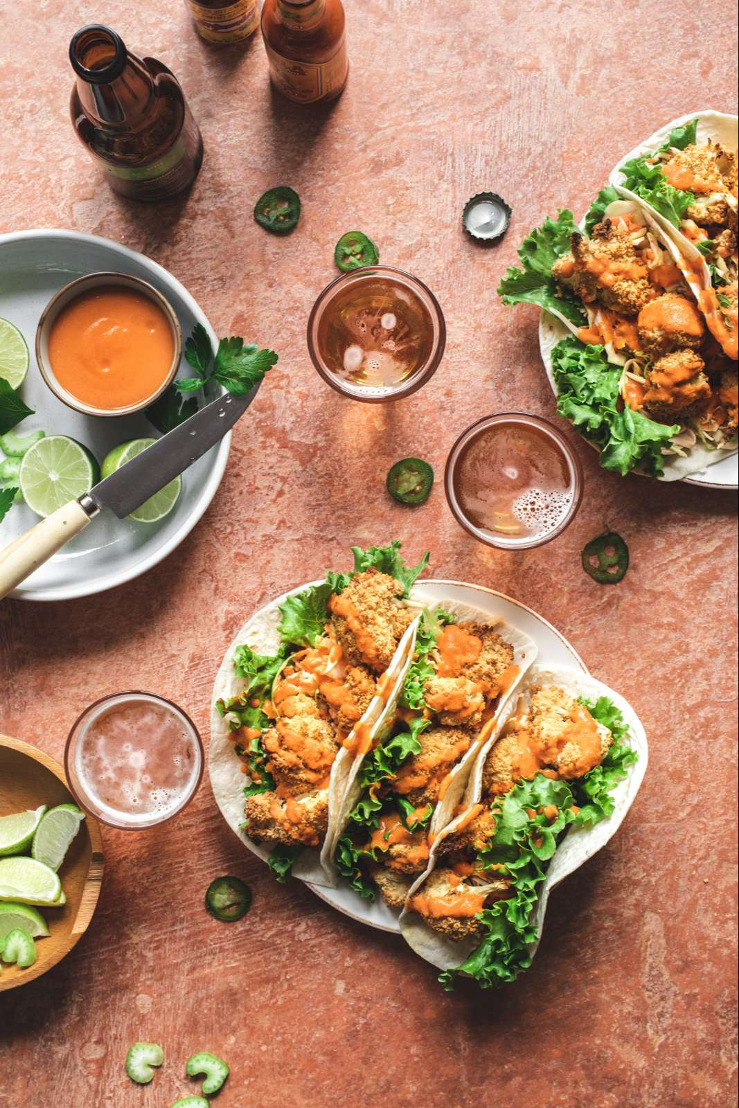 Hand pouring beer into a glass next to a plate of three buffalo cauliflower tacos and bowls of lettuce, jalapenos and extra buffalo sauce