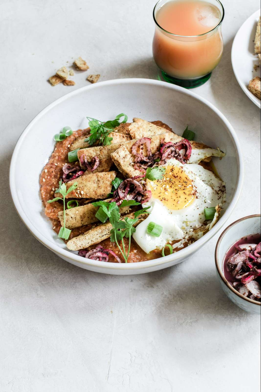 Close-up bowl of eggplant pitaquiles topped with a fried egg and sumac onions