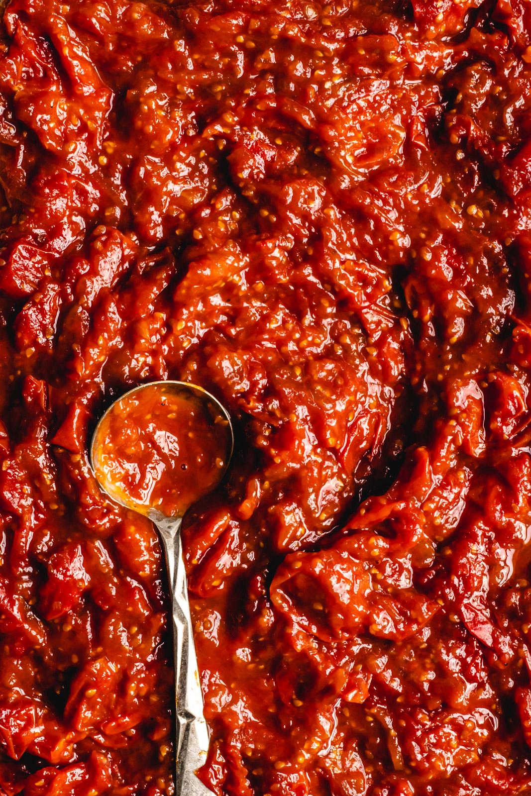 macro shot of cherry tomato harissa jam with a spoon