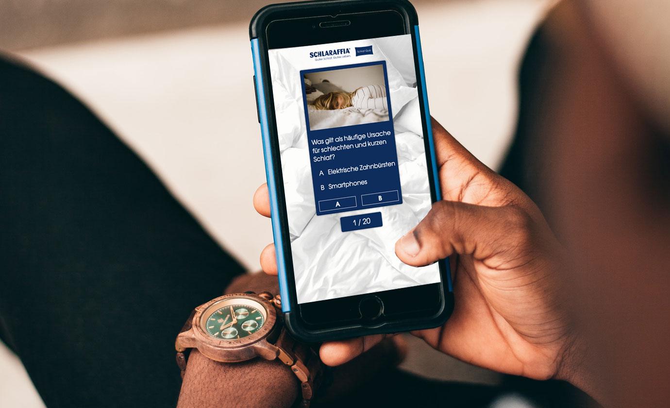 Mann mit Handy in der Hand schaut sich das Schlaraffia Quiz zum Welt-Schlaf-Tag an.