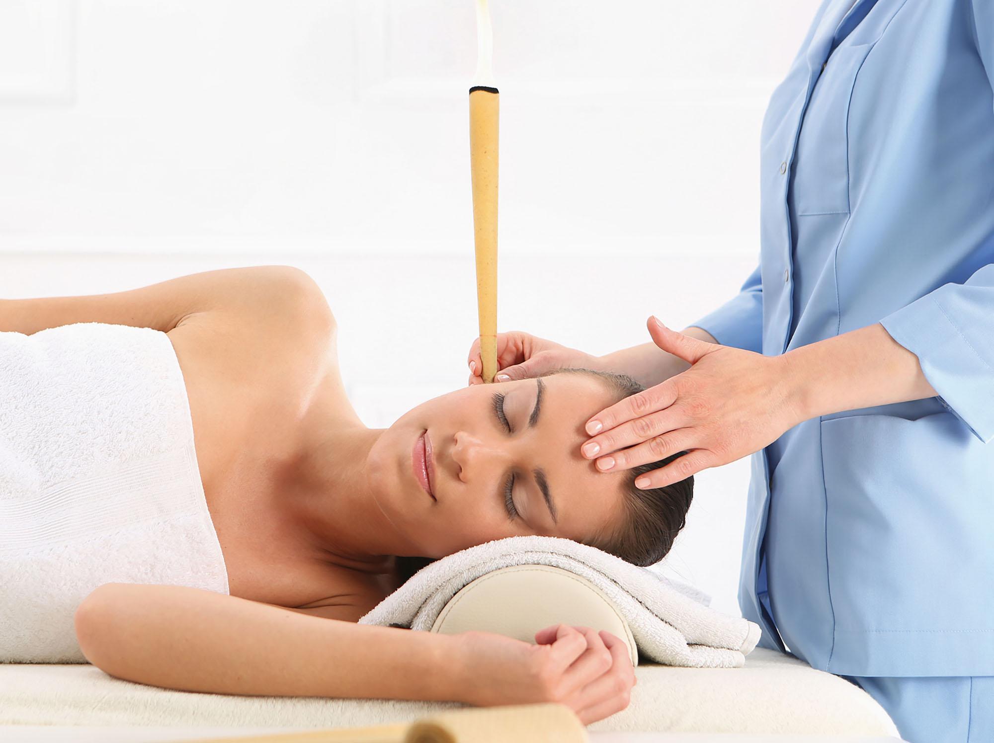 Eine Frau macht eine Ohrenkerzentherapie