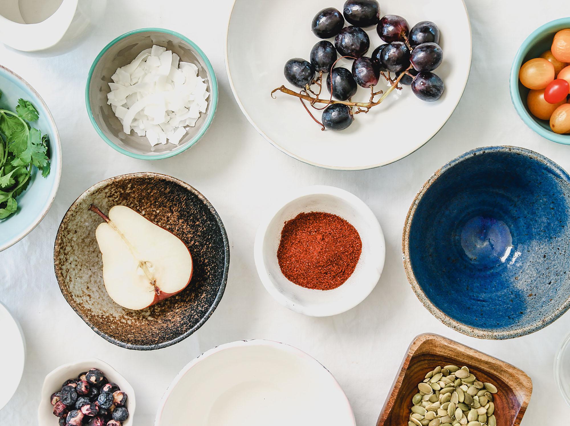 Verschiedene Schüsseln mit Obst, Gemüse, Reis und Getreide