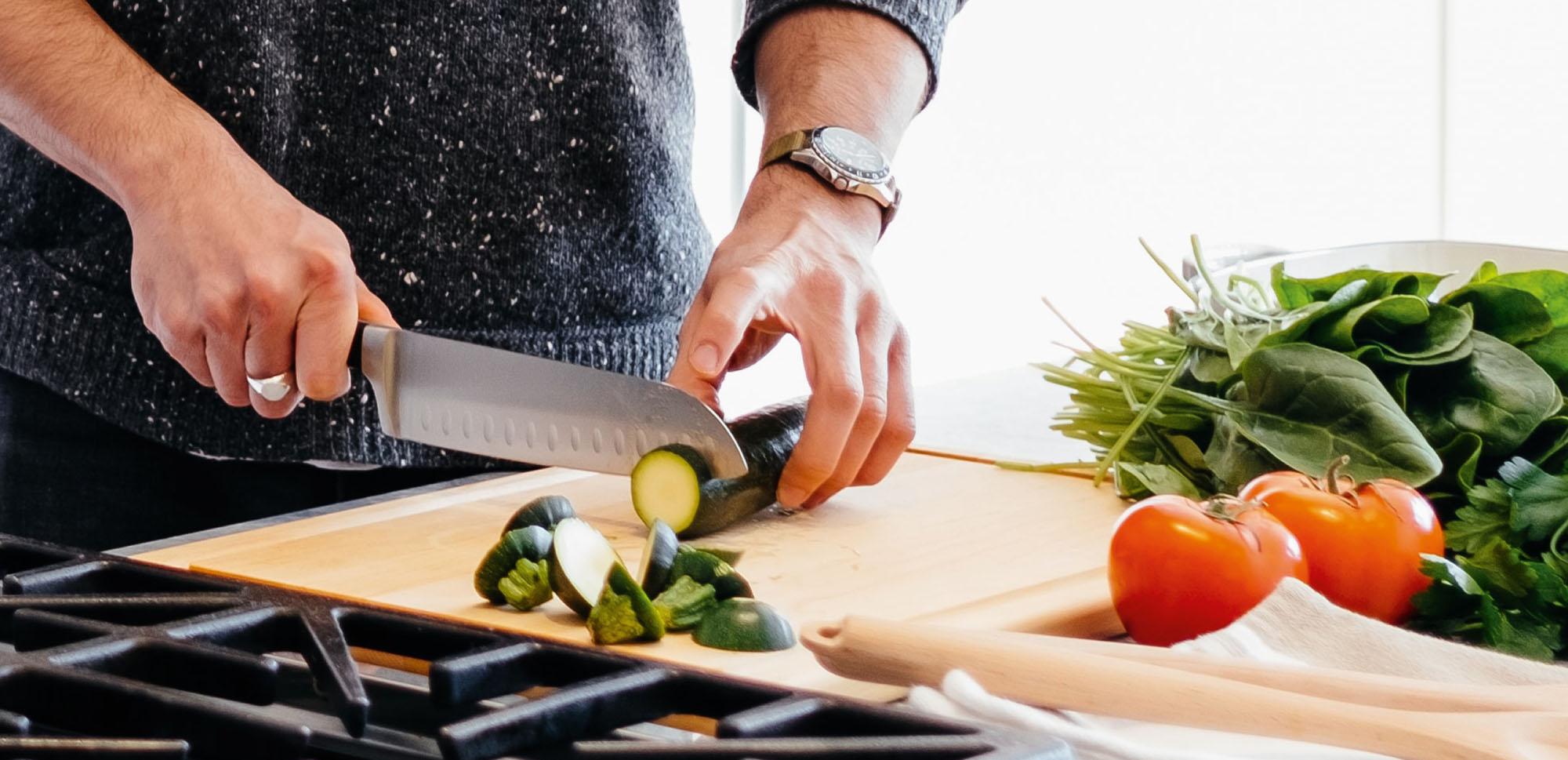 Mann schneidet Gemüse