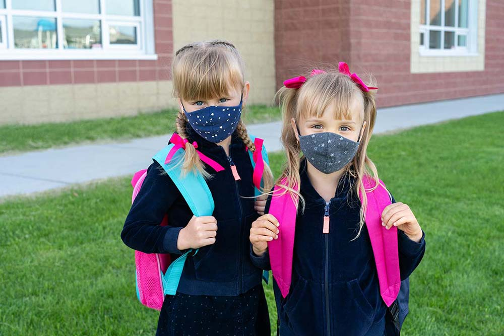 Two girls going back to school with masks on