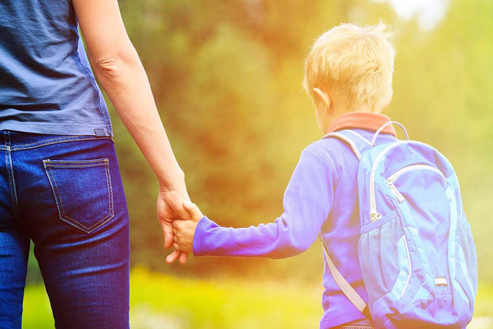 Woman and child walking and holding hands going back to school
