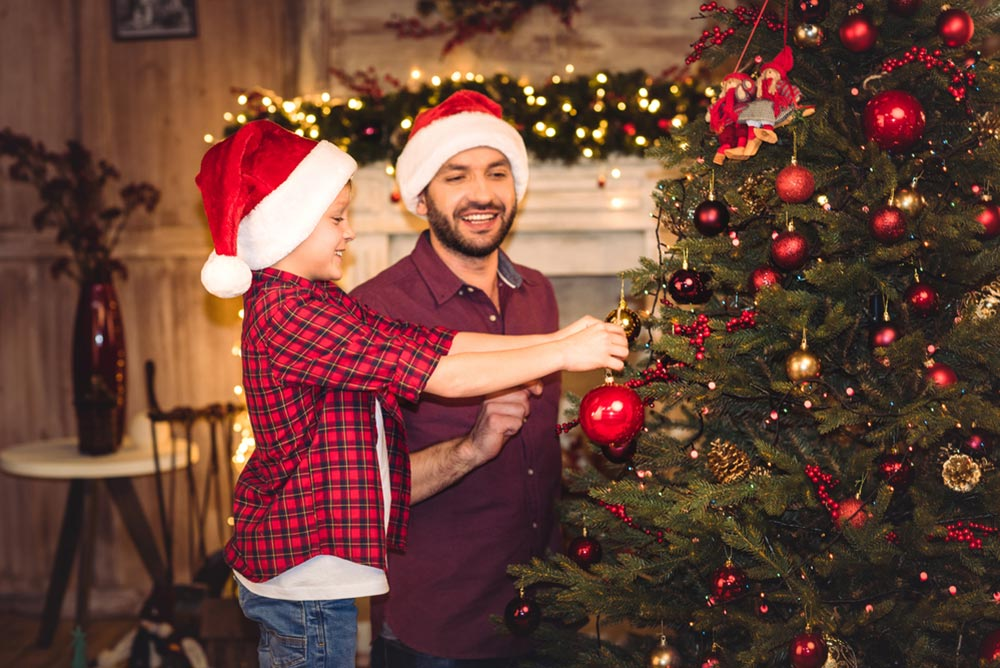 Father and son hanging ornaments on the Christmas Tree - Holiday Possession Schedule