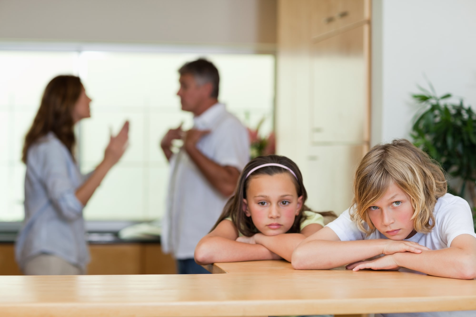 parents arguing in the kitchen with children nearby