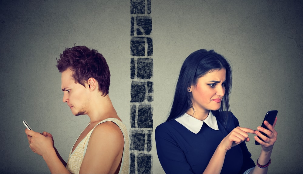 Divorce and social media Angry couple upset man and woman separated by wall on mobile phones