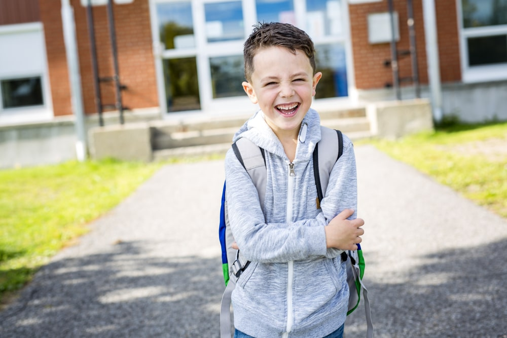 Student outside school standing smiling after changing schools