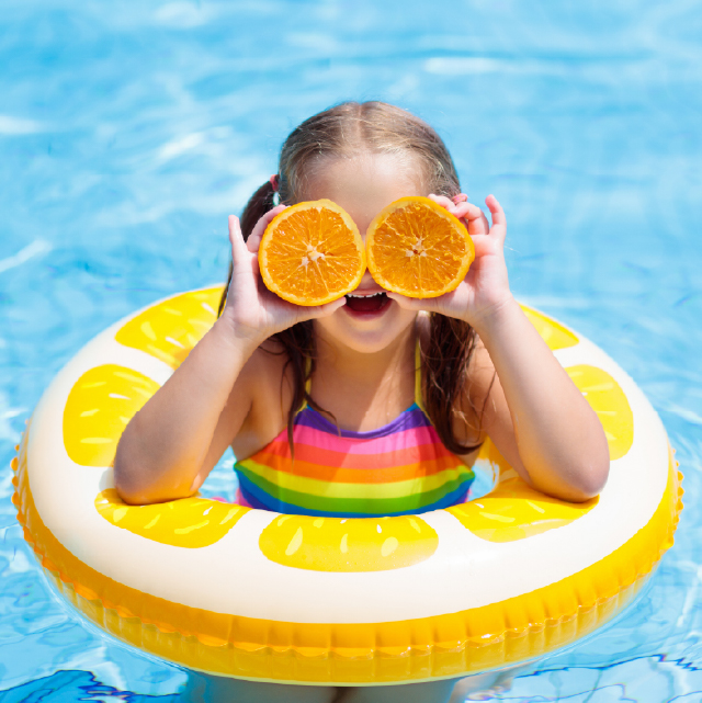 A little girls with a floatie in a pool holding orange slices on her eyes