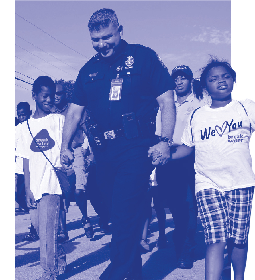 Police Officer holding hands with a few community kids.