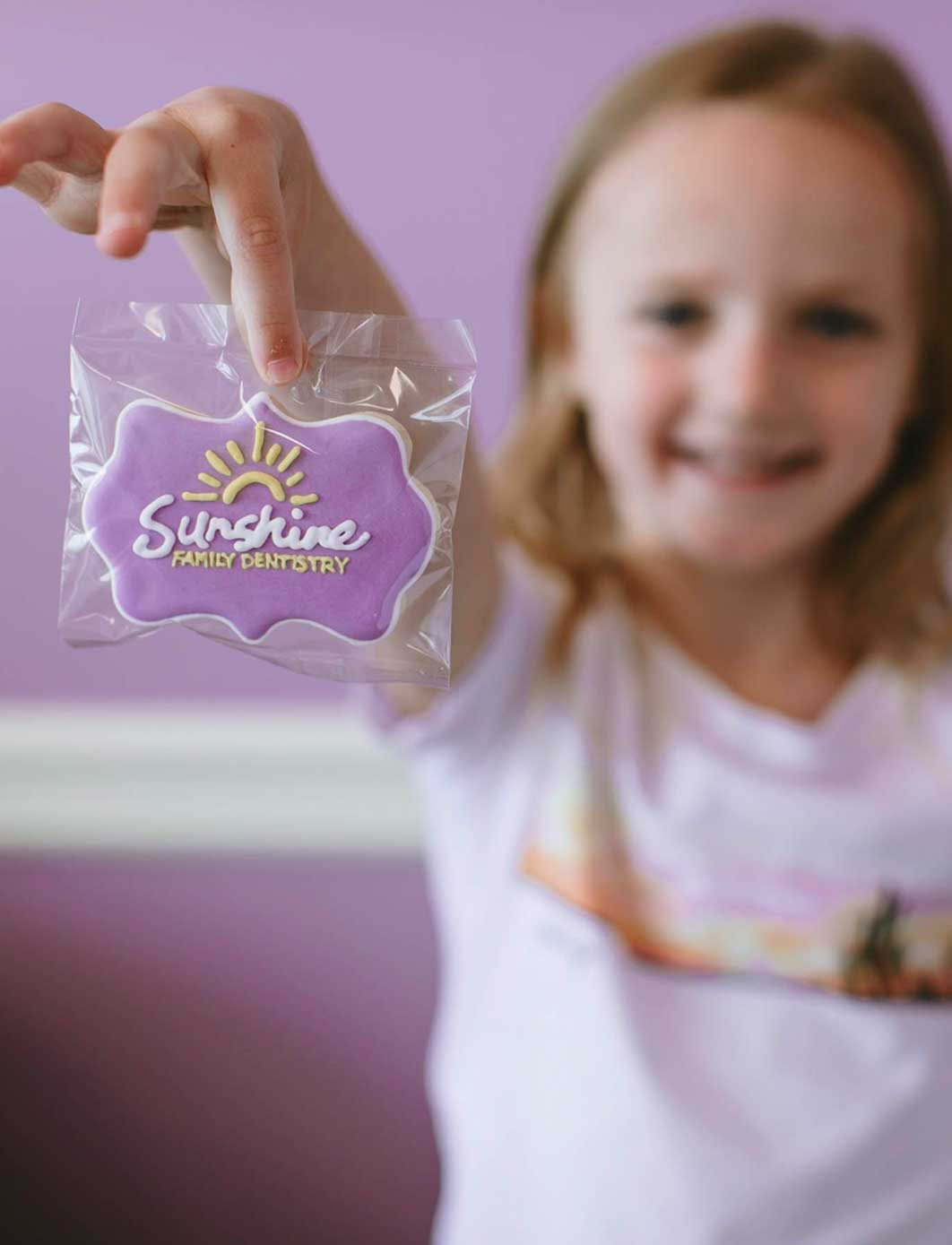 Photo of a girl holding a Sunshine Family Dentistry cookie