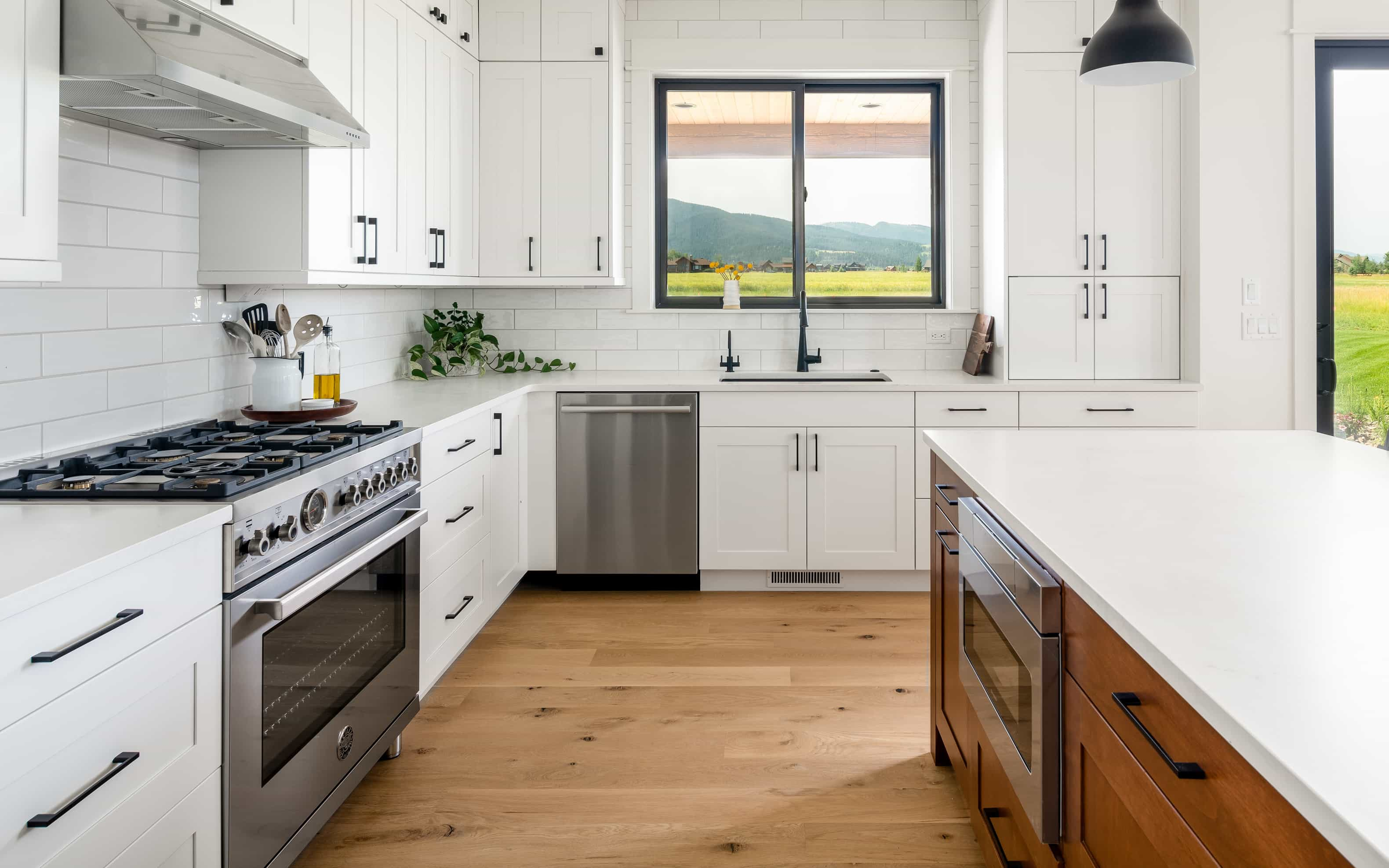 For this modern farmhouse, we created a clean, simple aesthetic through the use of white quartz, quartzite and ceramic subway tile. In the kitchen white quartz countertops were paired with white ceramic tile, white cabinetry and wood floors for this modern farmhouse look. The theme was carried into the bathrooms. Quartzite was used in the master bathroom and subway tile was used throughout, contributing to the clean lines and simple beauty of the space.
