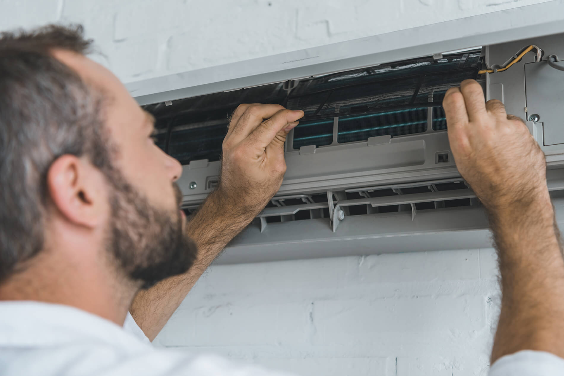 Photo of an HVAC repairperson fixing an AC unit