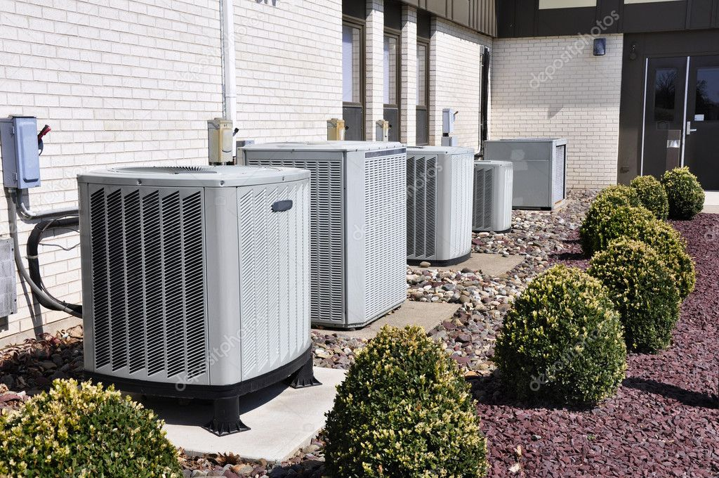 Photo of four AC units outside a house