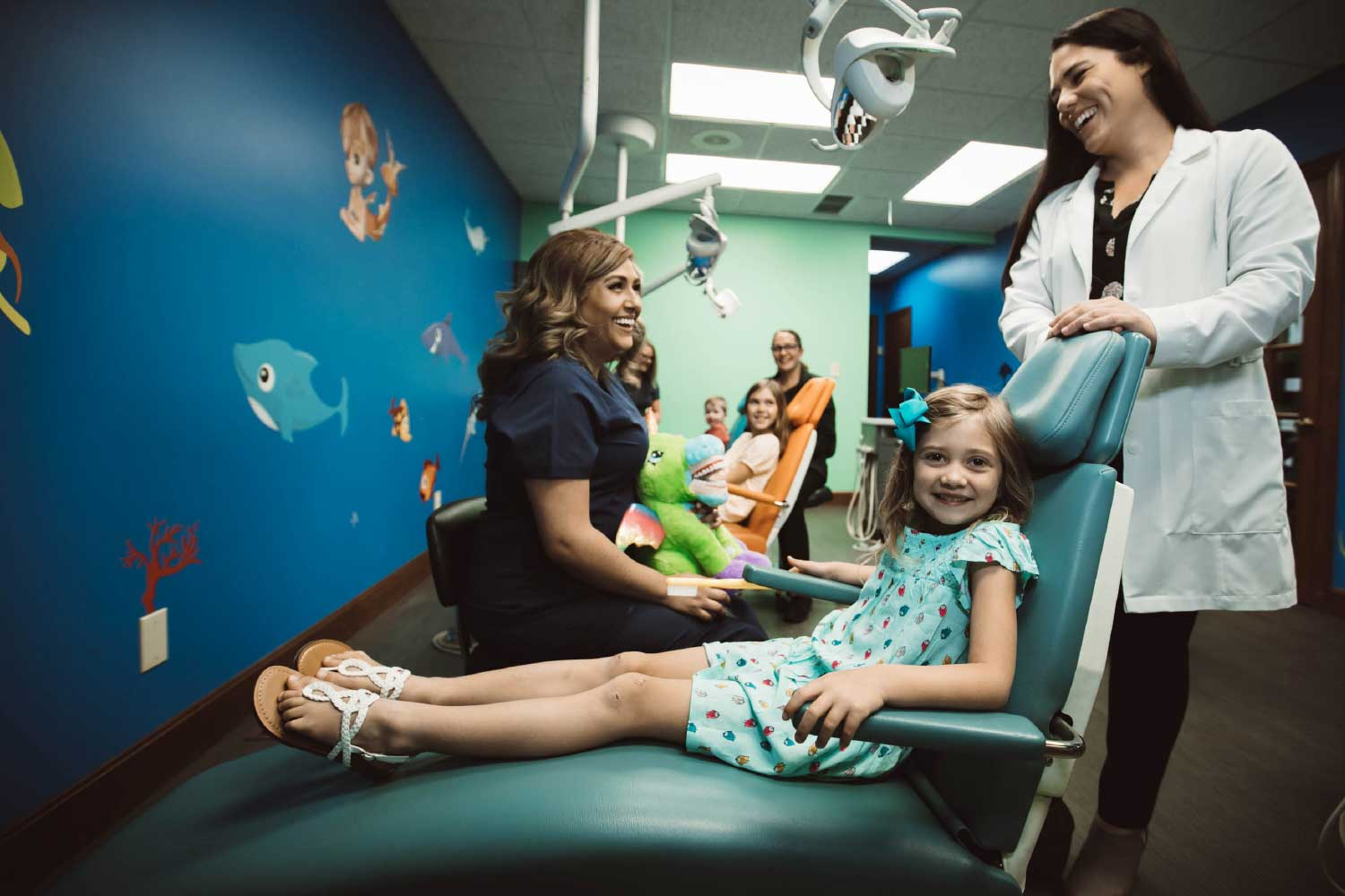 Photo of a smiling patient sitting in a dental char next to Dr. Myers and a team member